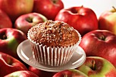 An apple muffin on red apples