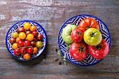 Zwei Teller mit verschiedenen Tomatensorten auf Metalluntergrund (Draufsicht)