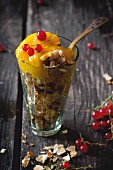 Mango sorbet with redcurrants and wafer crumbs in a glass on a wooden table