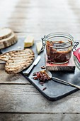 Tomato chutney in a jar and on a spoon, slices of bread and cheese