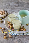 Pistachio milk in small glasses and a pastel blue jug with pistachios scattered around