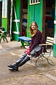 Frau mit roten Handschuhen in A-Linien-Kurzmantel, Wollrock und Stiefel