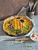 Colourful carrot quiche with sunflower seeds and a yoghurt dip