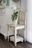 weiße Orchidee auf Holzstuhl mit weisser, abblätternder Farbe, darunter kleiner, gepolsterter Fussschemel