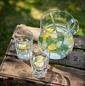 Zitronenwasser mit Gurke und Minze auf Holzkiste im Garten