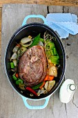 Leg of lamb with vegetables and herbs in a braising pot