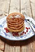 Gestapelte Pancakes mit Honig und Granatapfelkernen