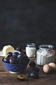 Verschiedene Kuchenzutaten (frische Pflaumen, Mehl, Eier, Zucker, Butter)