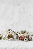 Cupcakes mit weißem Zuckerguss und Wachteleiern zu Ostern
