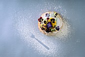 A sweet pastry with pistachio cream, pansies and icing sugar