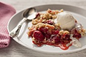 A portion of raspberry crisp (USA) with vanilla ice cream