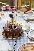 A birthday cake decorated with candles on a garden table