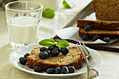 Sliced banana bread with blueberries and a glass of milk