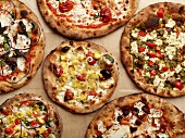 Pizzas with various toppings (seen from above)