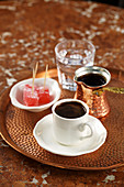 Turkish coffee with a glass of water and Turkish Delight on a copper tray