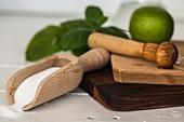 Stössel, Limette, Holzschütte mit Zucker auf Holzbrettchen