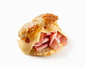 A cheese and ham croissant on a white surface