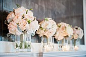 Bunches of roses and tea lights as decoration for a wedding