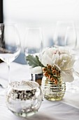 A silver tea light holder, a bunch of flowers and wine glasses on a table laid in white