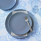 A place setting with blue plates and a fork (seen from above)