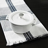A white pot on a napkin