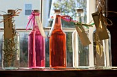 Homemade flavoured vinegar in bottles on a window sill