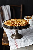 A whole apple and frangipane tart glazed with apricot jam on a cake stand