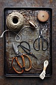 Various pairs of old scissors and kitchen twine on a baking tray