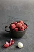 Lychees in a metal cup with a peeled lychee next to it