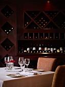 Gedeckter Tisch für Zwei vor einem Weinregal im Restaurant