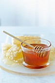 A glass of honey with a honey spoon and a honey comb in the background
