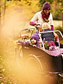 Mutter transportiert Kinder und Körbe fürs Herbstpicknick im Lastenfahrrad