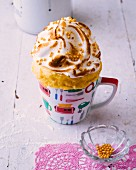 An orange mug cake topped with meringue and sugar sprinkles