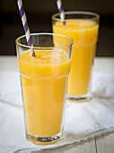Yellow exotic fruit smoothies in glasses with straws