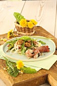 Spring salad with nuts, dandelion leaves, wild garlic, ham rolls and chicory