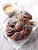 Poppyseed buns with plum jam and icing sugar served with a cup of coffee