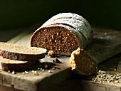 Dark spiced bread, sliced, on a chopping board