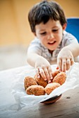 A child reaching for a supplì (fried rice croquettes)