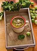 Green cabbage soup in a tin mug