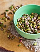 Shelled pistachios in a small bowl and next to it