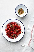 A bowl of cherries next to a bowl with stems and stones