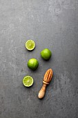 Limes, whole and halved, with a wooden juicer (seen from above)