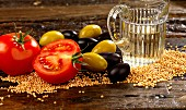 Ingredients for salad dressing with sesame seeds, tomatoes, olives and white wine vinegar