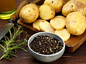 Peppercorns, rosemary and potatoes, whole and sliced