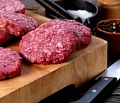 Raw wild boar burgers on a chopping board