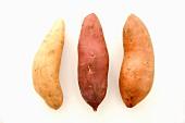 Drei verschiedene Süsskartoffeln vor weißem Hintergrund