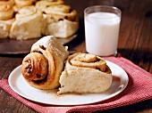 Two cinnamon buns on a plate served with a glass of milk