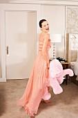 Junge Frau in Abendkleid hält rosa Plüschelefanten im Hotelzimmer