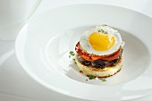A toast canapé with mushrooms, tomato and fried egg