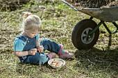 Kleines Mädchen mit frischen Hühnereiern auf der Wiese